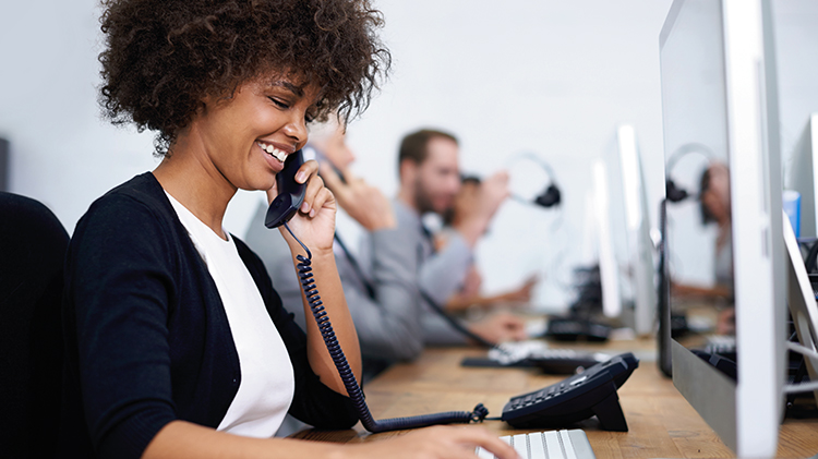 A smiling customer center employee talks on the phone—allow your employees to care for the customers as well as service.