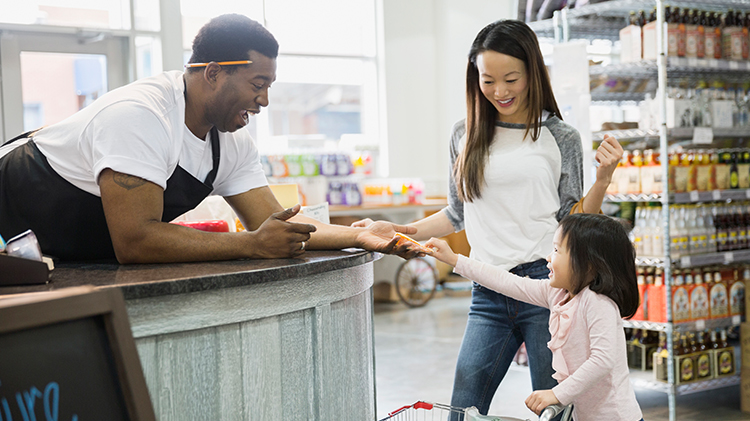 A grocery employee smiles and leans over his counter to engage a customer and her child.