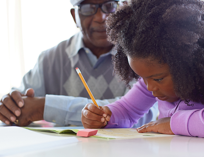 Little girl doing homework with her dad.