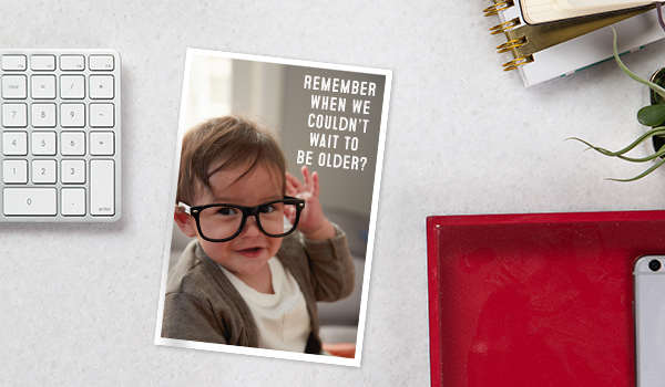 A toddler wearing adult-size glasses dons a funny retirement card, representing the Hallmark card selection available.
