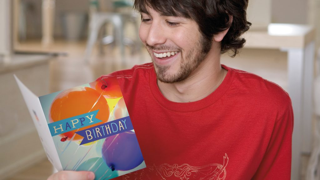 A man smiles as he reads a birthday card—a card that didn't come from a relative but rather your company.