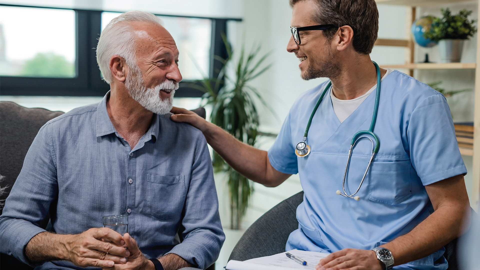A doctor smiles and chats with his male patient—friendly interactions are the experiences health plans desire for members.