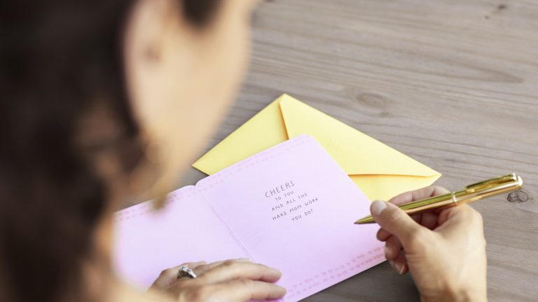 A business executive gets ready to write a personal note inside a Hallmark business greeting card.
