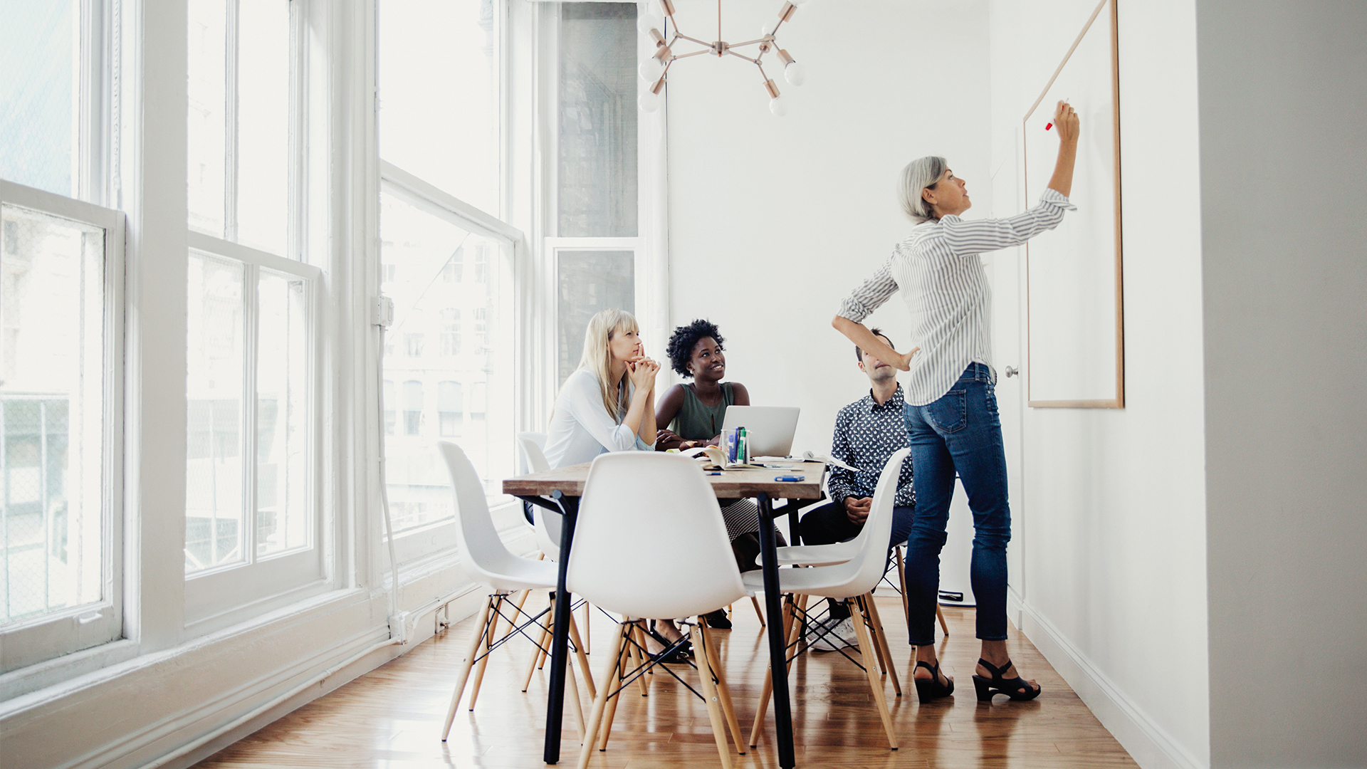 A woman stands in front of a whiteboard while three people watch in a conference room—perhaps marketers reviewing data.