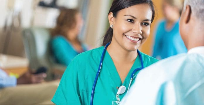 Nurse in blue scrubs smiling at person she's talking to.
