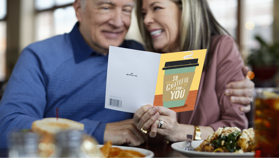 Older couple smiling while reading greeting card from a business.