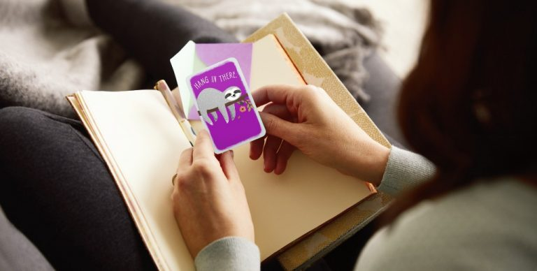 Person holding a Hallmark Hang in There card.