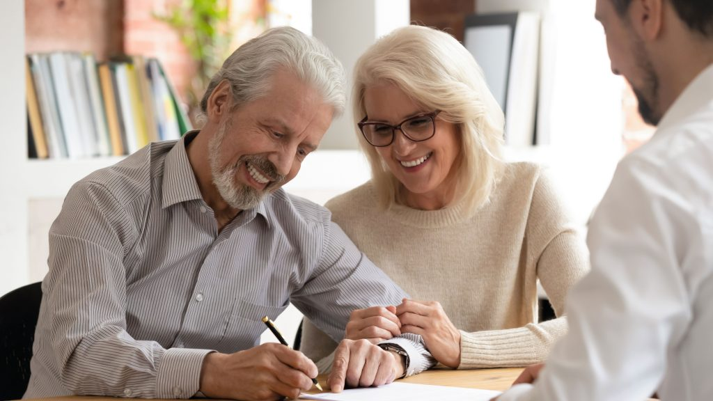 Happy older couple at desk meeting with insurance or wealth management rep signing a paper at rep's desk.